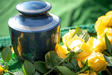 Urn with yellow roses, at an outdoor funeral with space for text