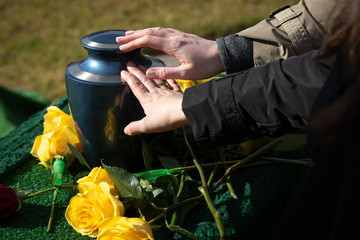 Two hands touching a cremation urn at a funeral