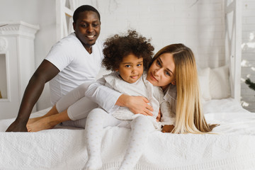 Happy interracial couple with their little daughter at home