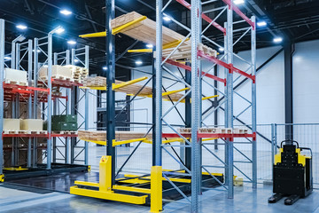 Stock. Equipment for a modern warehouse. Warehouses. Storage of lumber. The tree lies on racks. Responsible storage. A small loader next to the racks. Loading of goods. Logistic Services