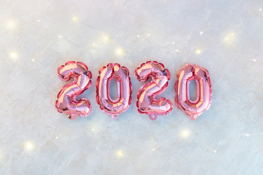 Pink numbers 2020 on a white background. A garland of stars shimmering with colorful lights.