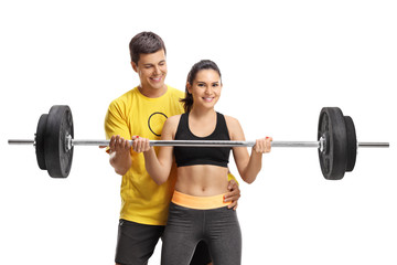 Young woman lifting a barbell with the help of a fitness coach