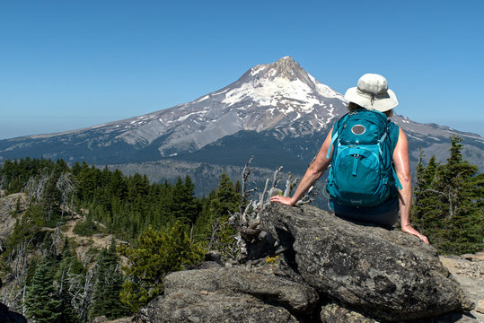 A mature woman hiker sites on a rock with her back to us and enjoys the view of Mt. Hood from Lookout Mt. There is a clear blue sky and bright summer sunlight.