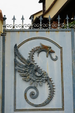 Metallene Drachenfigur an einem Eisentor