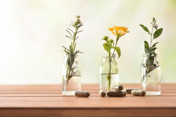 Natural herbal medicine capsules on wooden table with tree jars