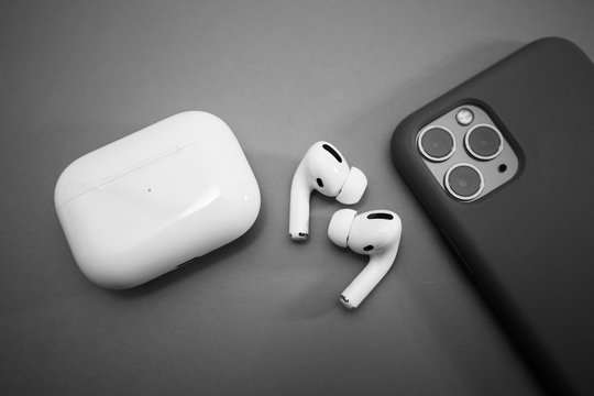 Paris, France - Oct 30, 2019: Charging case and the new iPhone 11 Pro next to New Apple Computers AirPods Pro headphones with Active Noise Cancellation for immersive sound