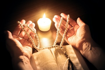 Praying hands, Islamic background . The holy Koran under candlelight . Book in candlelight