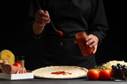 The chef cooks Italian pizza, topping with sauce. Freeze in the air. Against the background of pizza ingredients. Black background