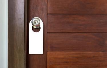 Door Hanger Acrylic Shape Blank on dark wooden door background.  for your mock up and advertising design.