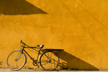 Spoed Fotobehang Fiets Bicycle leaning on yellow wall at Hoi An city in Vietnam
