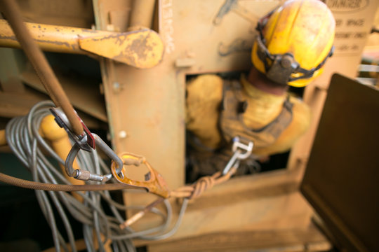 Unfocused of rope access confined space worker wearing safety harness, helmet connecting three two one pulleys rescue system into back of his safety harness  loop prior entering into confined space