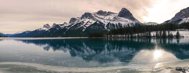 Wide Panoramic Winter Landscape of Frozen Mountain Lake and Rugged Snowcapped Peaks above Canmore, Alberta in Canadian Rockies near Banff National park Fototapete