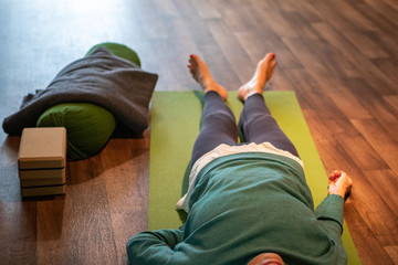 Selective focus from people lying on top of yoga mats on the floor following instructions from a yoga and mindfulness teacher