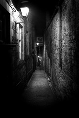 A dark creepy narrow European alley at night, surrounded by bricks and cobblestone. Illuminated only with some street lamps. Concept of scared or being alone and frightened