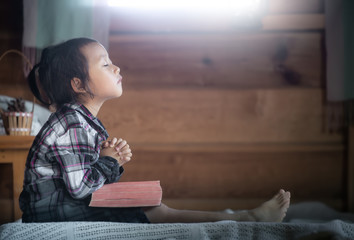 asian little girl reading and praying on Bible in morning at home. christian concept.