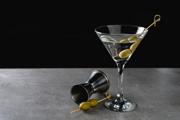 Drink Dry Martini with Green Olives on Stone Background.
