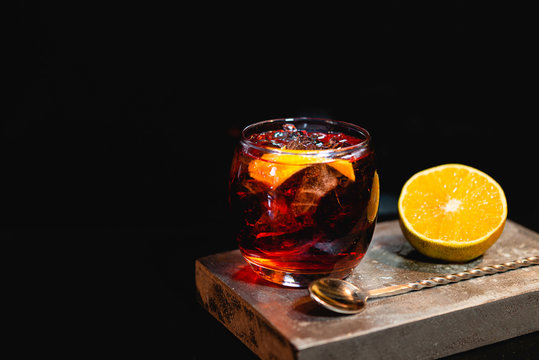 Boulevardier cocktail on stone background in gray color.