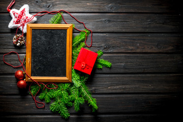 Photo frame with Christmas decorations and fir branches.