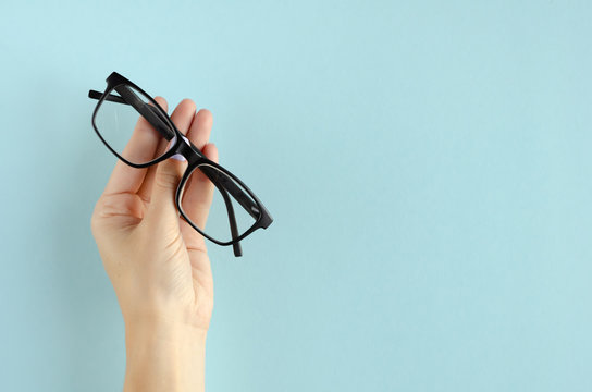 Hand with eyeglasses composition on blue background.