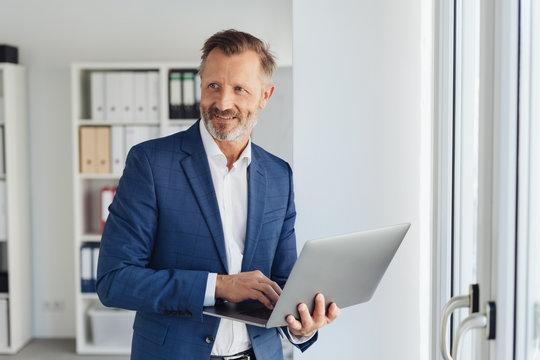 Smart businessman using a handheld laptop computer