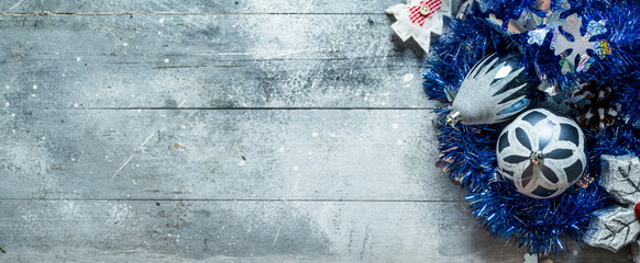 Christmas decorations with blue tinsel and a pine cone.
