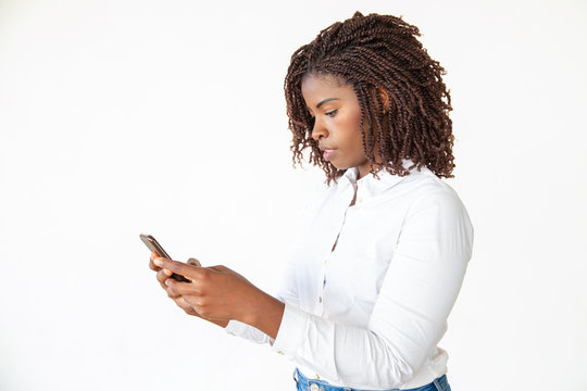Focused employee texting message on smartphone. Young African American office worker standing isolated over white background. Mobile phone using concept