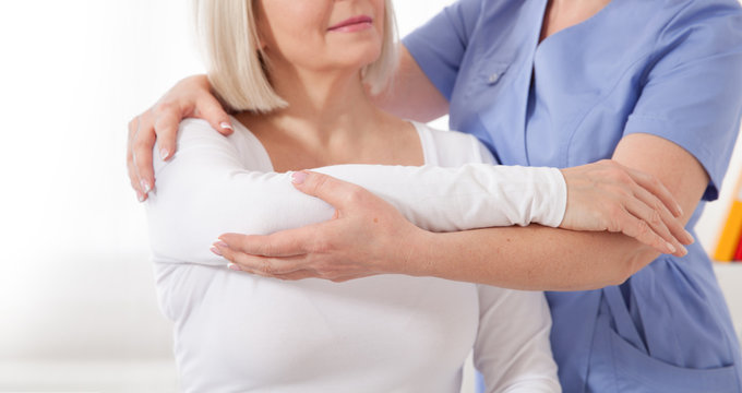 Physiotherapist working with middle aged patient in clinic