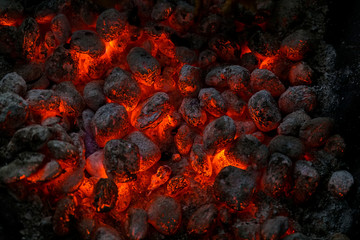 Coals of a bonfire burning at night .