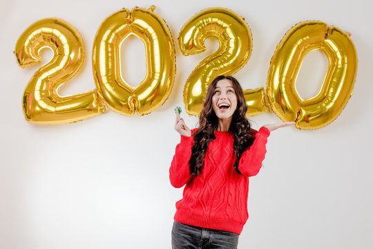 woman in red sweater holding green poker chip from online casino in front of 2020 new year balloons