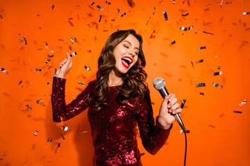 Portrait of charming pop start girl have karaoke party on her prom sing song hold microphone enjoy loud music wear maroon outfit isolated over orange color background confetti falling Wall mural