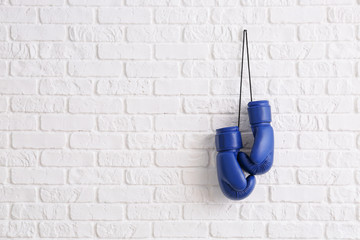Pair of boxing gloves hanging on brick wall