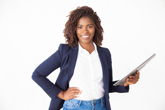 Happy female professional holding documents, keeping hand on hip, looking at camera. Young African American business woman standing isolated over white background. Confident leader concept