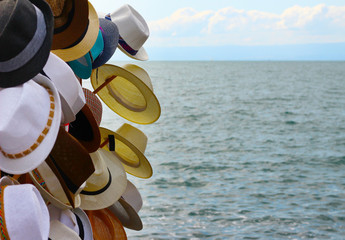 Hats for sale at a touristic market place near a lake in summertime