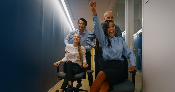 A group of carefree workers are having fun with office chairs after finishing their work.