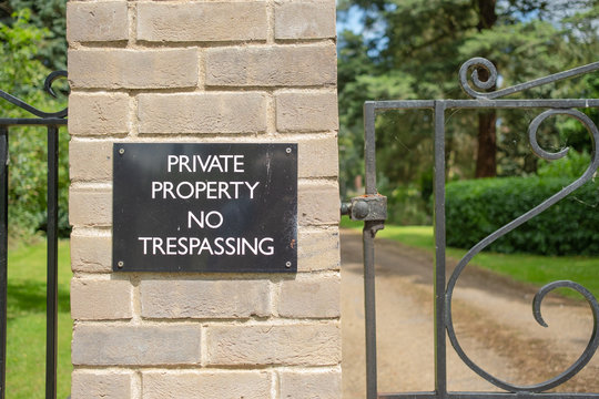 Detailed view of a large Private Property sign seen attached to the bricked entrance to a large, private house. Landscaped gardens are seen beyond the gate