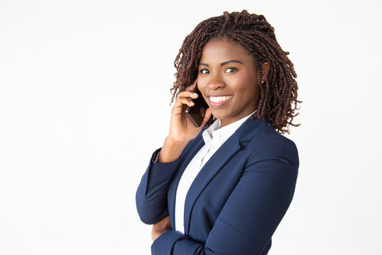 Happy successful consultant talking on mobile phone, looking at camera. Young African American business woman standing isolated over white background. Business communication concept