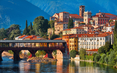 Bridge Ponte degli Alpini at river Brenta Bassano del grappa Italy. Panoramic view at old town with vintage building and tower and wooden bridge at background Alpine mountains scenic landscape. Fototapete