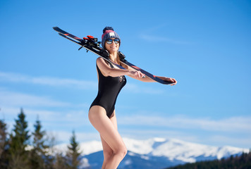 Smilling girl in black swimsuit, hat and sun glasses, standing with skis under sun at ski resort. Blue sky, forests, mountains on the background. Ski season and winter sports concept