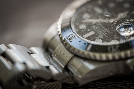 Close-up, shallow focus of a luxury, Swiss manufactured men's mechanical diving watch showing droplets of water on the face and strap.