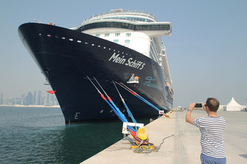 A foreign tourist takes pictures of a cruise ship Mein Schiff 5, at Doha Port in Doha