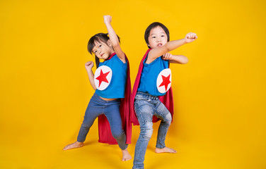 Portrait of asian little boy and girl playing pretend to superhero. Happy young toddler brother and sister wearing hero costume, education childhood lifestyle, back to school concept