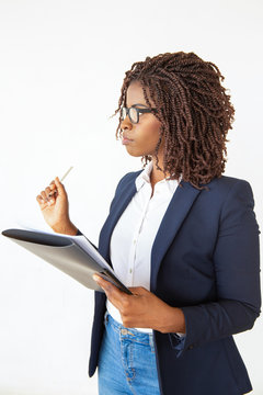 Serious focused secretary taking notes, holding pen and folder with papers, looking at away. Young African American business woman posing isolated over white background. Assistant job concept