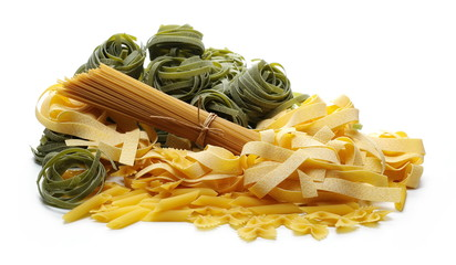 Raw pasta pile with pappardelle, tagliatelle, penne rigate, farfalle and integral spaghetti isolated on white background