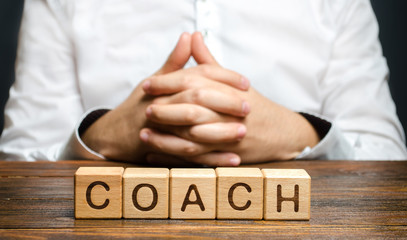 The inscription Coach and a man sitting with his hands clasped in a lock. Trainer and mentor. Self improvement. Achieving goals through training and guidance. Skills development