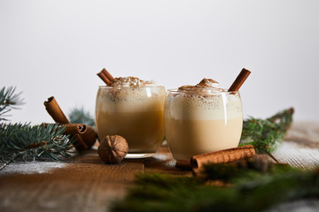 selective focus of eggnog cocktail with whipped cream near cinnamon sticks and spruce branches on...