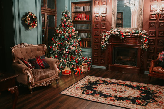 Classic living room and library New Year interior. Magic glowing Christmas tree, carpet, decorated fireplace and mirror, cozy armchair and gift present boxes in dark at night. Festive holiday evening