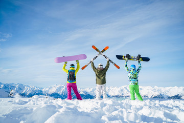 Photo from back of three snowboarders with their hands on snow resort
