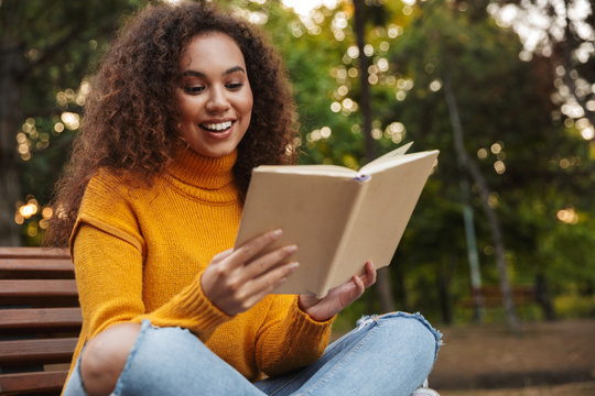 Beautiful curly woman sit in park outdoors reading book.