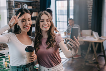 young, cheerful businesswoman taking selfie on smartphone with cheerful colleague holding coffee to...