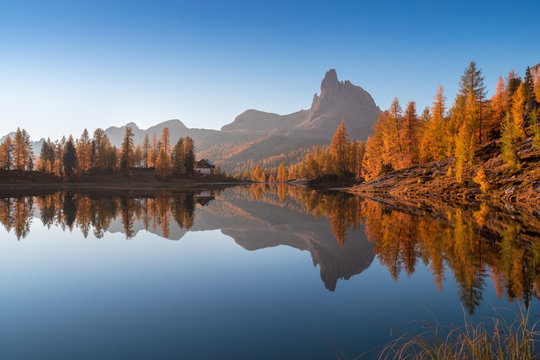 Autumn view of Lake Federa in Dolomites at sunset. Fantastic autumn scene with blue sky, majestic rocky mount and colorful trees glowing sunlight in Dolomites. Dolomite Alps with yellow larch trees